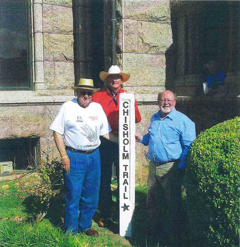 : Three men standing next to a 5 foot tall white post labeled Chisholm Trail