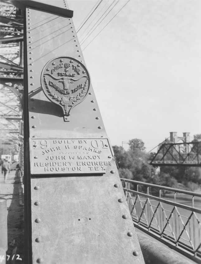 Round metal marker attached to a bridge saying Going Up the Texas Chisholm Trail 1867