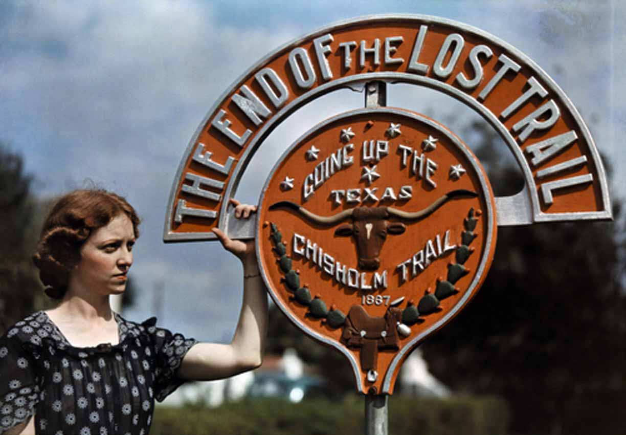 Woman standing next to a round metal marker saying The End of the Lost Trail - Going Up the Texas Chisholm Trail 1867