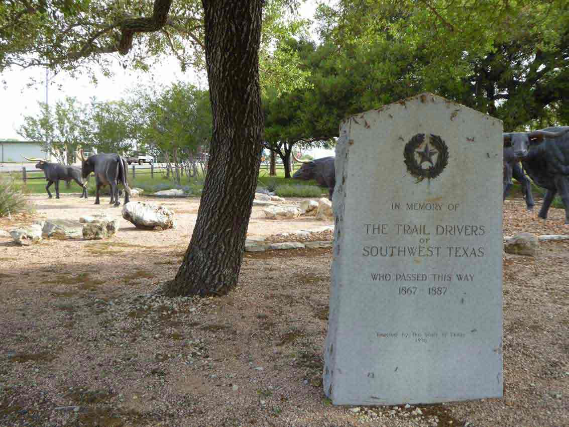 "Granite marker saying ""In Memory of the Trail Drivers of Southwest Texas who passed away 1867 – 1887"" in a park with full size bronze longhorn cattle"